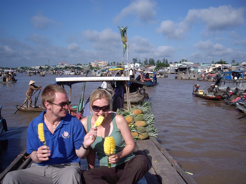 Tourists taste fresh fruit in Cai Be floating market