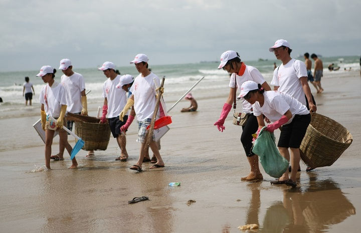 Tourists picking up trash on the beach of Cat Ba Island