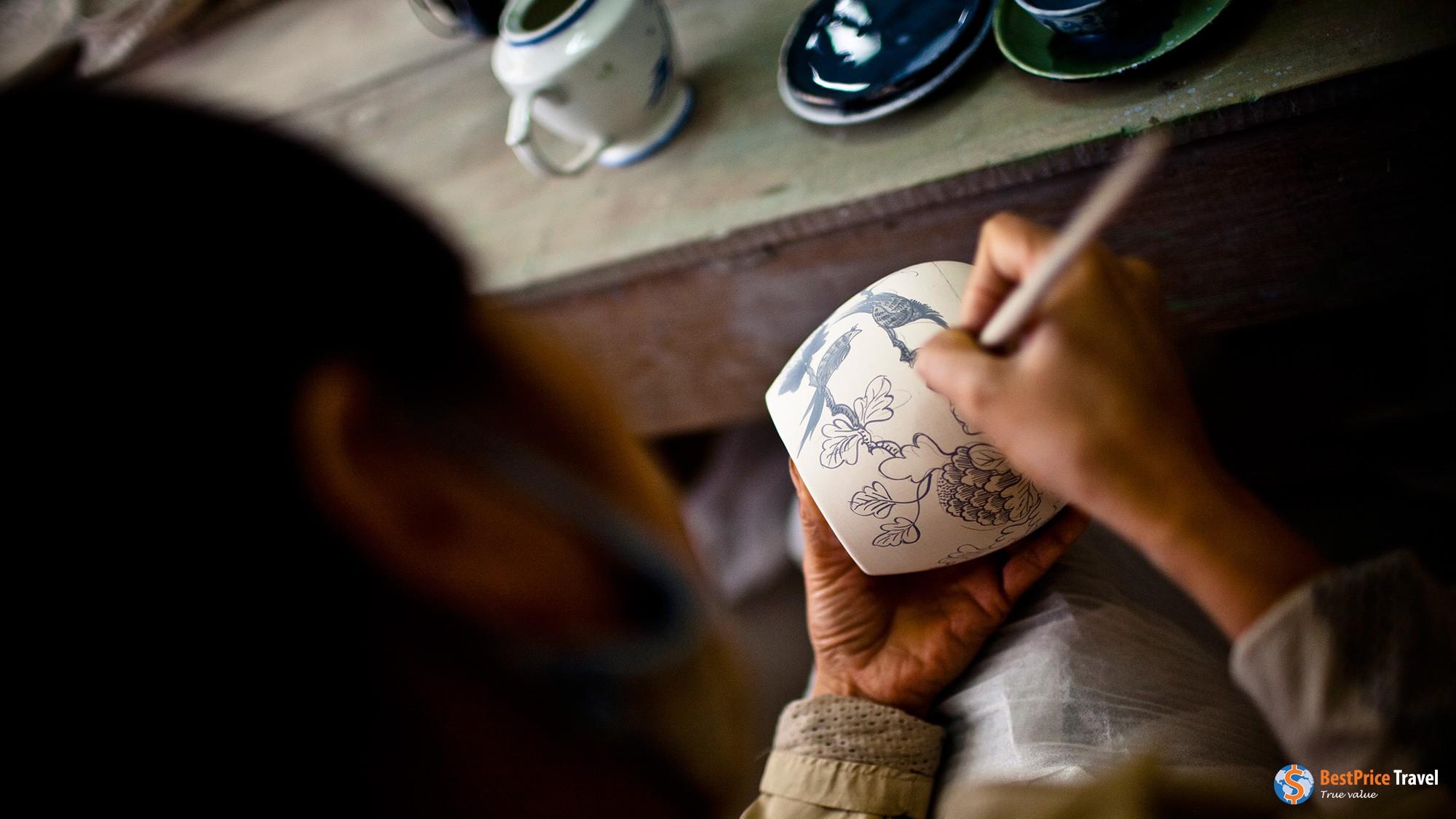 Artisan decorating a ceramic vase.