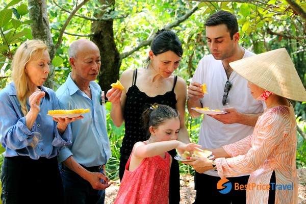 Tourists taste fresh tropical fruits in Mekong Delta