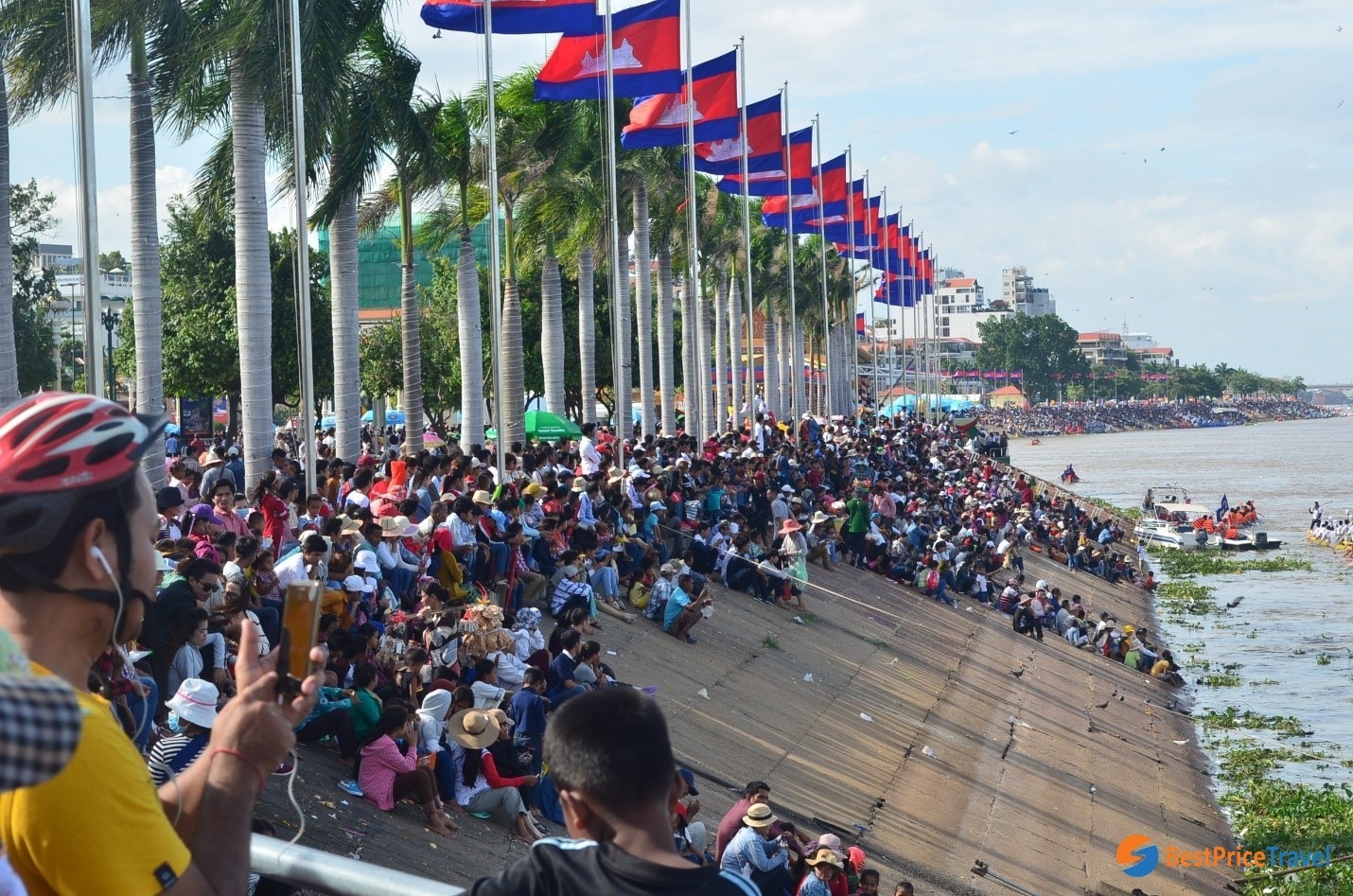 Spectators on the riverbank are cheering for their teams in rowing festival