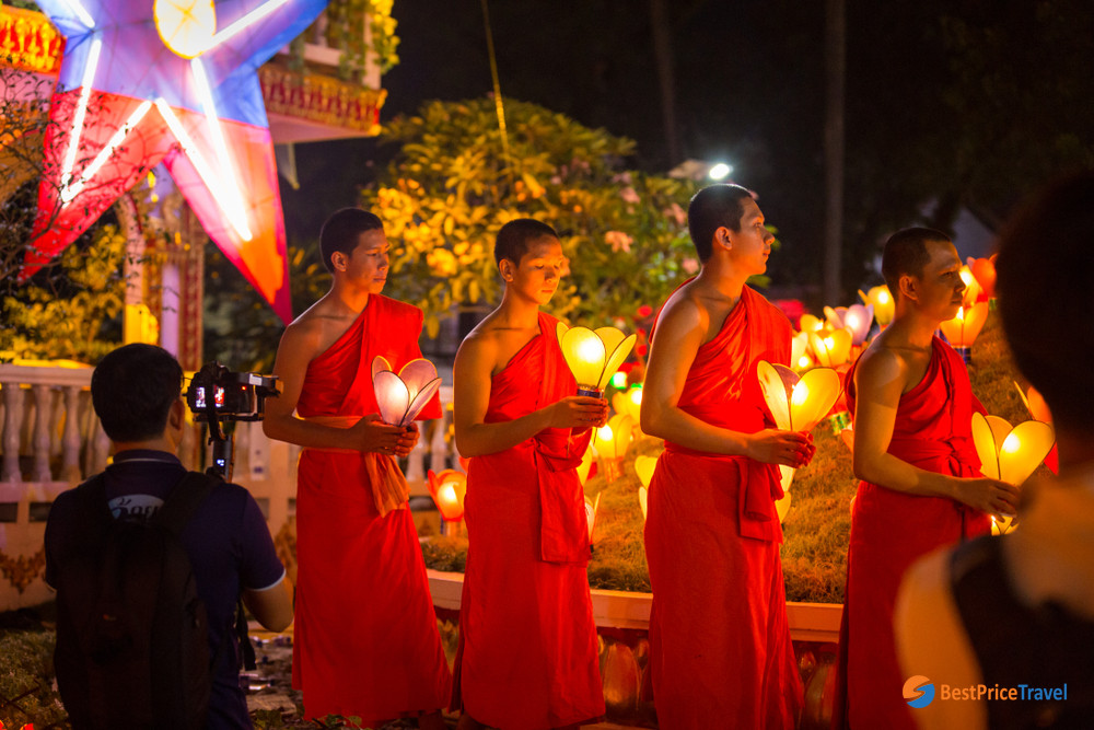 Monks are praying at a temple in Awk Phansa Festival