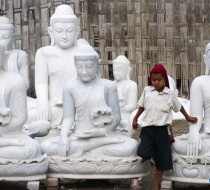A Local Boy Passes Through A Group Of Buddha Statues Lining The Street In Mandalay.