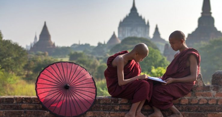 Young Monks With The Temple Strewn Skyline Of Bagan In The Background.